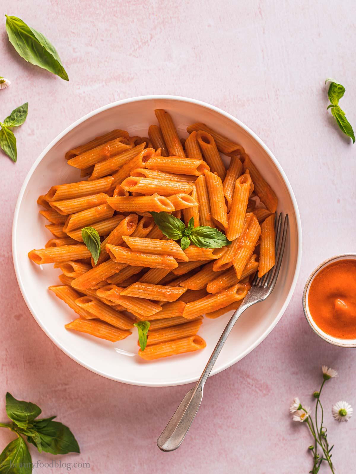 plate with creamy vegan ROASTED RED PEPPER PASTA and basil piatto di pasta conSALSA ai PEPERONI arrostiti e basilico