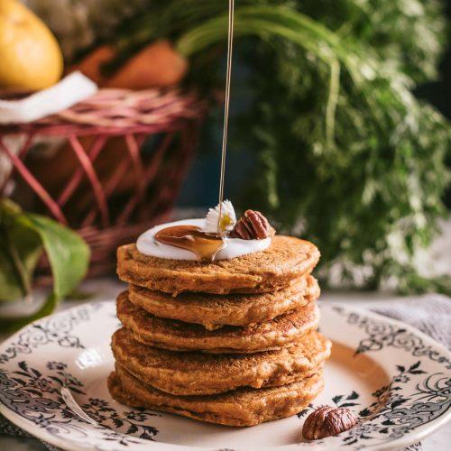 Stack of vegan carrot cake pancakes with maple syrup for a healthy breakfast piatto con pancake vegani alle carote integrali con sciroppo d'acero per una sana colazione