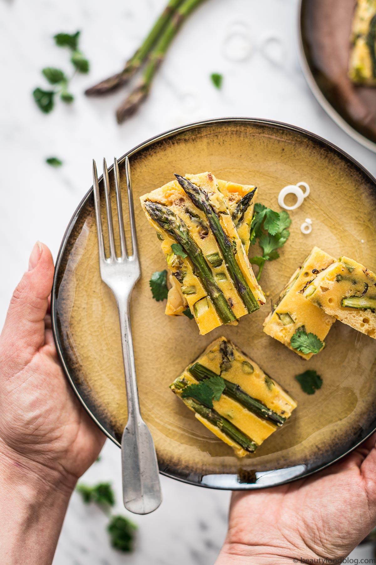 mani con piatto con fari frittata di ceci e asparagi plate with vegan Chickpea asparagus frittata