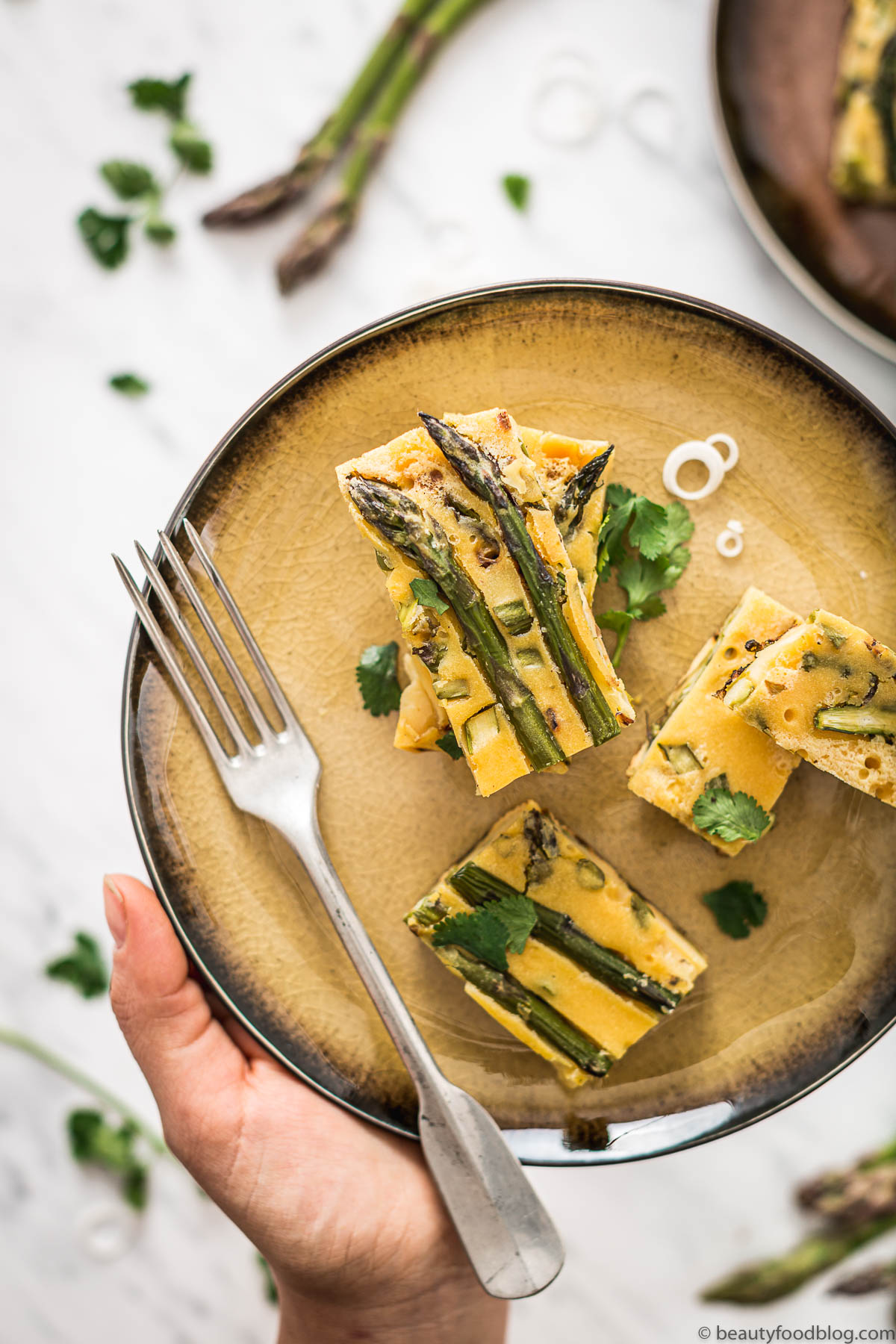 mano con piatto con fari frittata di ceci e asparagi plate with vegan Chickpea asparagus frittata