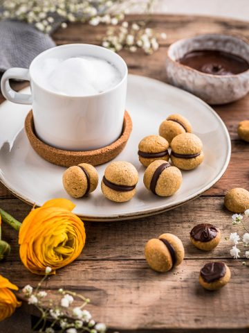 tazza cappuccino con baci di dama vegan su tavolo lady's kisses Italian Hazelnut Cookies with a cup of whipped milk