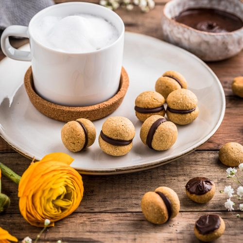tazza cappuccino con baci di dama vegan su tavolo lady's kisses Italian Hazelnut Cookies with a cup of whipped milk