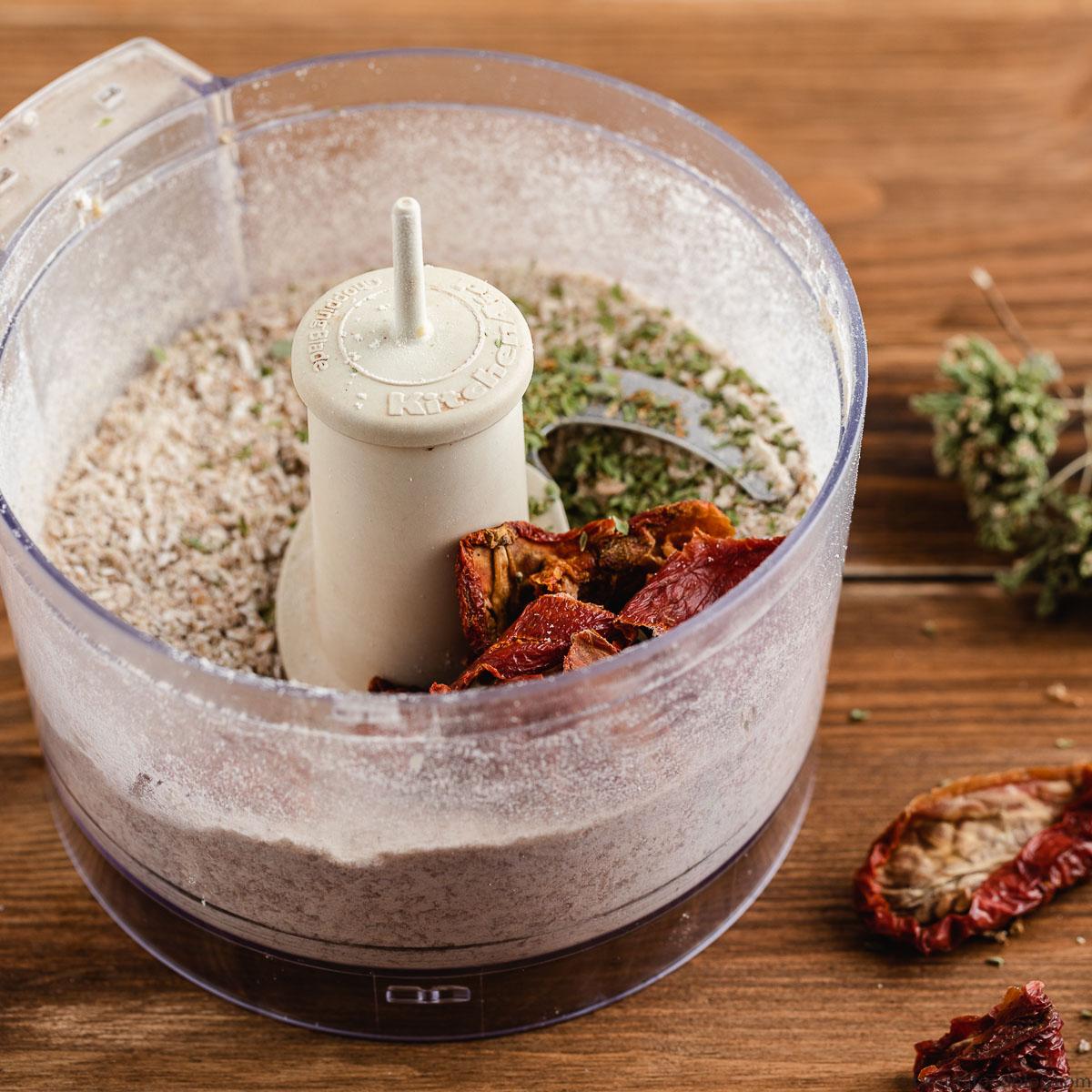 robot da cucina con ingredienti frullati e pomodori secchi food processor with flours and dry ingredients blended and sun-dreid tomatoes