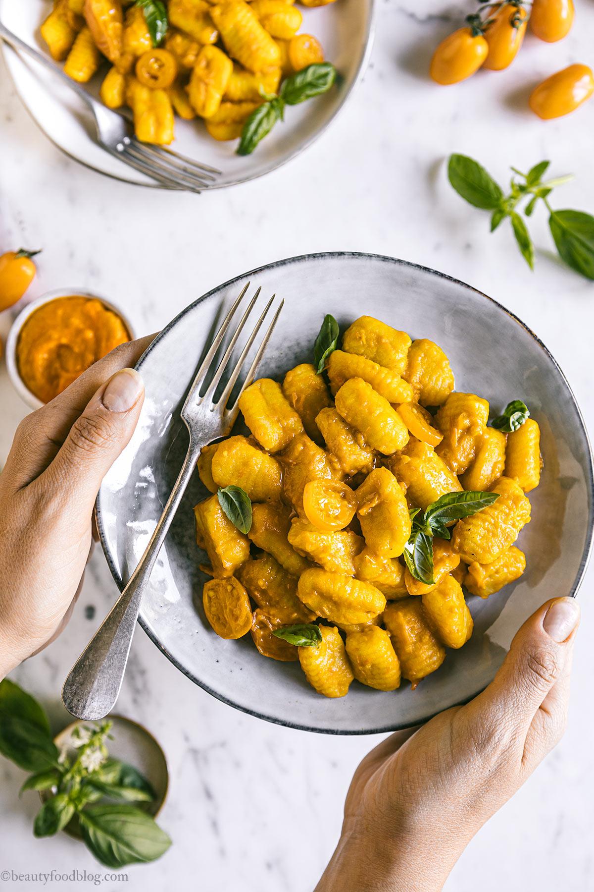 mano con piatto e gnocchi ai pomodorini gialli hand holding dish with vegan gnocchi with yellow tomato sauce
