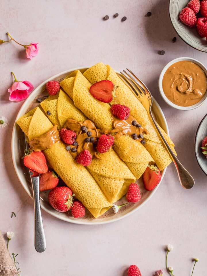 piatto con Crespelle con Farina di Ceci burro di anacardi frutta cioccolato plate with Gluten-free Vegan Chickpea Crepes berries almond butter and chocolate chips