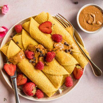 piatto con Crespelle con Farina di Ceci burro di anacardi frutta cioccolato plate with Gluten-free Vegan Chickpea Crepes berries almond butter and chocolate chips